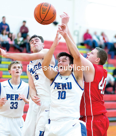 Peru's Tom Matthews (center left) and Justin LaPorte (10) compete with Saranac's Zauch Faus for control of a rebound during the championship match of the Muggsy's Tip-Off Classic. (GABE DICKENS/P-R PHOTO)