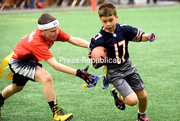 Peyton Viau (17) of Team Blue looks for running room with Bryce DeAngelo of Lake City Equipment trying to grab his flags during a U10 flag-football game at Crete Memorial Civic Center in Plattsburgh. This is opening week for all flag-football divisions, with the season continuing into next year. (ROB FOUNTAIN/STAFF PHOTO)