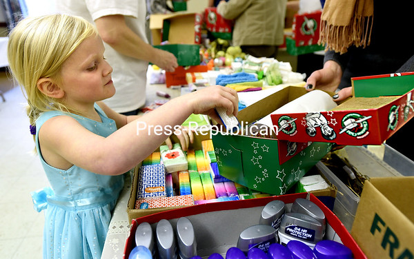 Iris McKinley, 5, places items into boxes for Operation Christmas Child during a box-packing party at Christ & St. John's Episcopal Church in Champlain on Sunday. Donors fill shoeboxes with different items of need and fun, which are sent to children in poverty-stricken areas in the world. Samaritan's Purse runs Operation Christmas Child. (ROB FOUNTAIN/STAFF PHOTO)