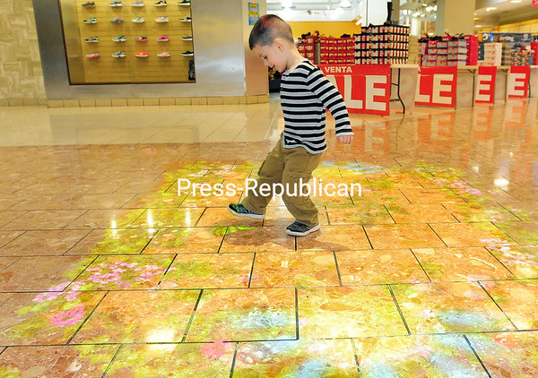 ROB FOUNTAIN/STAFF PHOTO 12-8-2016<br /> Odhran Leon plays some soccer Monday on the new interactive projector outside Gander Mountain at Champlain Centre mall in Plattsburgh. The projector has 50 sensor-driven images that shine on the floor, challenging kids to play games.