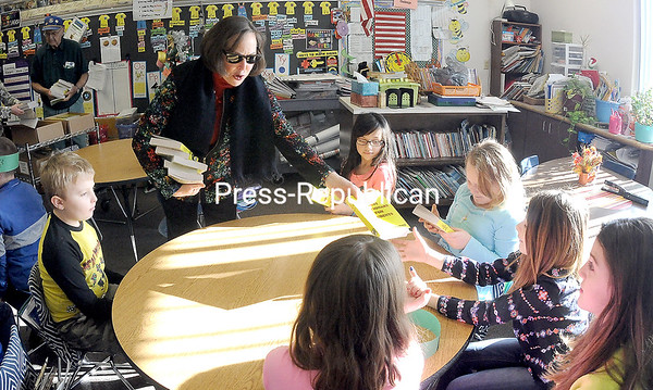 ROB FOUNTAIN/STAFF PHOTO 12-28-2016<br /> Kiwanis member Nancy Church hands a new dictionary to Momot Elementary School third-grader Raelyn Miller. More than 70 students at the Plattsburgh school received a copy of the reference book to help them with their homework and classwork for years to come. The club also gave dictionaries to students at Seton Academy and Beekmantown Elementary School. This is one of many projects the Kiwanis Club does for area children throughout the course of the year.