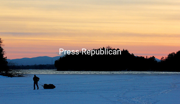 MIKE PITTS/P-R PHOTO 12-27-2016<br /> Lance Russell of Peaslyville makes his way to shore on Cumberland Head Bay in Plattsburgh. A seasoned angler on and off the ice, he said it's not unusual to bring in a bucket of perch after a day on the ice. And since he recently retired, he is able to have plenty for supper and the freezer.