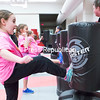 GABE DICKENS/P-R PHOTO 4-12-2016<br /> Eryn Hicks, 8, of Peru, lands a kick in the self-defense workshop taught by Dave Boise, of Fred Villari's of Plattsburgh, during the recent Shine On! conference at SUNY Plattsburgh. The annual 24-hour event, now in its sixth year, is put on by a group of female students at the college and aims to teach young girls resiliency; media and marketing literacy; and communication skills. Nearly 50 college-age mentors and 200 girls ages 8 through 11 participate each year.