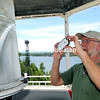 With his cellphone, Mark Malchoff takes a photo of the Bluff Point Lighthouse's working light Sunday during the Bluff Point Lighthouse Restoration Celebration on Valcour Island.<br /> <br /> rob fountain/staff photo 7-26-16