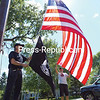 GABE DICKENS/P-R PHOTO<br /> John Carpentieri, who served in Vietnam with the U.S. Army in the 25th Infantry Division and as a door gunner with the 25th Aviation Battalion, helps Danny Kaifetz, owner of Adirondack Flagpoles, raise a 12-by-8-foot American flag and a POW flag on a 60-foot steel flagpole, believed to be over a hundred years old, for the first time in decades at the Carpentieris' property in Peru. Keeseville Volunteer Fire Department brought their 100-foot tower truck, with mutual aid from Peru Volunteer Fire Department, for a training exercise to help Kaifetz replace the rope, called a halyard, before the flags could be raised.