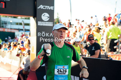 JACK LADUKE/P-R PHOTO 7-24-2016 State Trooper Ed Gibbs of Ray Brook crosses the finish line at the 18th Ironman Lake Placid triathlon Sunday. More than 2,700 athletes registered for the annual event, which began with two 1.2-mile swim loops in Mirror Lake, followed by two 56-mile bike loops and a 26.2-mile run through the town and around the lake. For more on Ironman Lake Placid, see page B1.