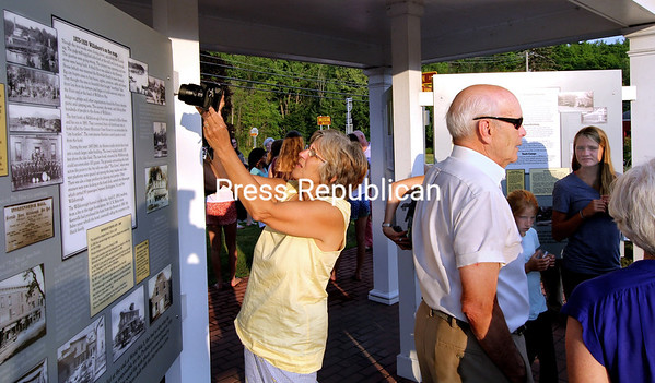 """CELEBRATING WILLSBORO HISTORY<br /> ALVIN REINER/P-R PHOTO 7-26-2016<br /> Visitors check out the newly erected history kiosk at the Willsboro History Center. A standing-room-only crowd attended the recent opening ceremony for the kiosk, which features eight large panels depicting the town's 250-year history. Much of the $44,000 used for the facility's construction came through the J.C. Kellogg Foundation and Patty Paine. The kiosk was dedicated to Ken and Marilyn Cole """"for their love of the beauty and history of Willsboro, Lake Champlain and the Adirondacks."""" Willsboro Town Historian Ron Bruno collaborated with graphics designer Rob Powell and editor Mary Bell to create the historic panels. The kiosk is located by the State Route 22 bridge spanning the Boquet River and Paine Memorial Library in Willsboro."""