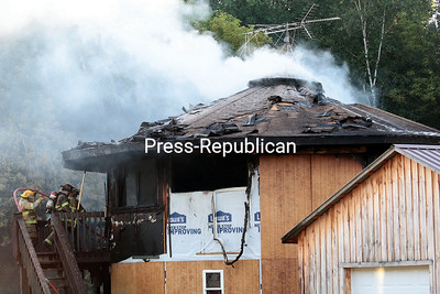 GABE DICKENS/P-R PHOTO 7-24-2016 Smoke pours from the roof of a home at 814 State Route 9 in Keeseville Saturday evening as firefighters knock down the last of the flames shooting from the top floor of the structure.