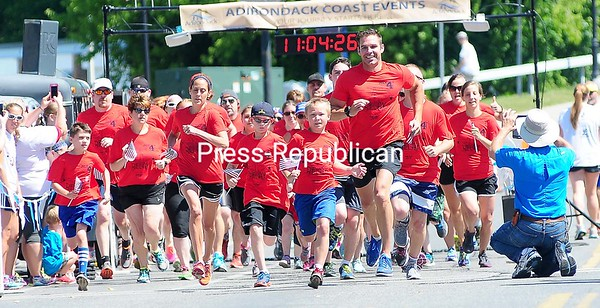 ROB FOUNTAIN/STAFF PHOTO  7-5-2016<br /> Runners sprint out of the starting gate Monday for the second-annual Red, White and Blue Relay on City Hall Place in Plattsburgh. The 1-mile race is part of the City of Plattsburgh's Fourth of July Celebration.