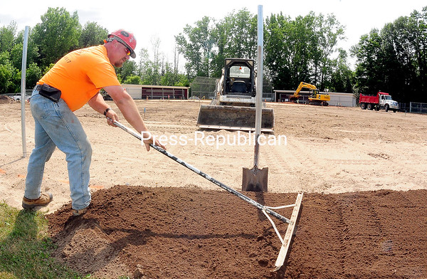 ROB FOUNTAIN/STAFF PHOTO 7-23-2016 Eric Sayles of Fuller's Excavating levels off dirt near the outfield fence of the SUNY Plattsburgh softball field. Fuller's is updating the field to meet NCAA requirements to make it regulation. Upgrades include 2,000 feet of outfield and infield drainage, making the outfield fence deeper, making the fence 6 feet around the field, a warning track, a new infield dirt mix and grass. Target date for the project to be finished is Aug. 11.
