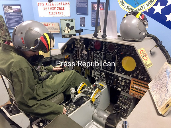 ROBIN CAUDELL/STAFF PHOTO A Quebecois translates the flight checklist from English to French as he explores the Cockpit Procedures Trainer at the Plattsburgh Air Force Base Museum.