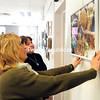 """Donna Austin (left) and Marilyn Kretser hang up the image """"6 Sheep"""" at the Strand Center of the Arts. (ROB FOUNTAIN/STAFF PHOTO)"""
