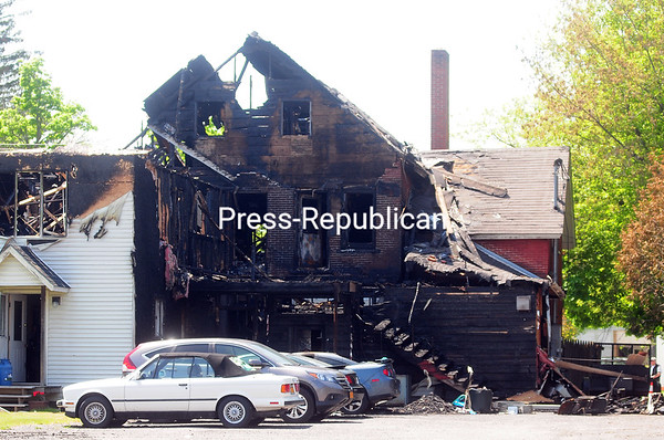ROB FOUNTAIN/STAFF PHOTO  5-24-2016<br /> Plattsburgh City Police sit by the remains of the apartment house at 220 Margaret St. on Monday morning. The investigation into the cause and origin of the conflagration that killed two tenants early Sunday was continuing.