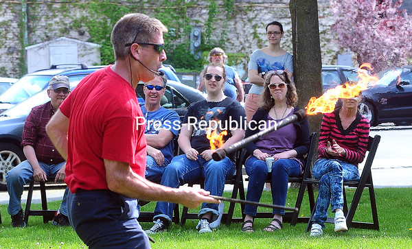 ROB FOUNTAIN/STAFF PHOTOS  5-23-2016 Steve Gratto juggles flaming clubs in Plattsburgh's Trinity Park during the Destination Downtown event held Sunday. The business-promotion event was the follow-up to Destination Downtowns held last May and September. Organized by the Plattsburgh Downtown Association, the events encourage participating businesses to attract customers with discounts, giveaways and other promotional activities. The event Sunday also featured street performers, musical acts and the opening of the Macdonough Monument for visitors to look inside.
