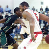 GABE DICKENS/P-R PHOTO 11-18-2016<br /> Plattsburgh State's Jonathan Patron goes behind-the-back to avoid Elm's defender Keeshaun King during the Caridinal's 126-101 win over the Blazers Friday night during their home opener at Memorial Hall in Plattsburgh.