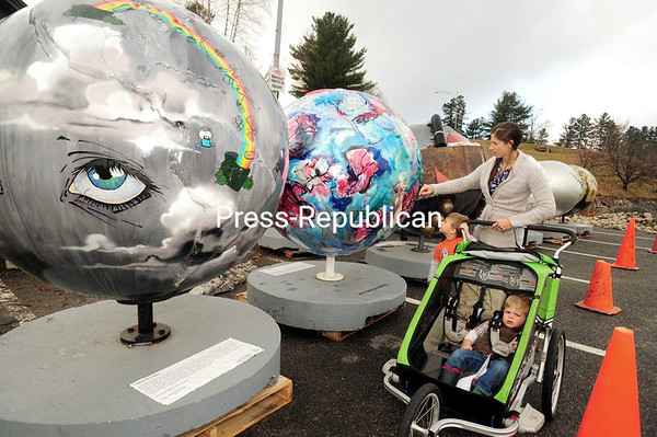 """JACK LaDUKE/P-R PHOTO 11-30-2016 Kate Briskie of Lake Placid and her sons, Elijah, 4, and Levi, 2, stop in the Lake Placid municipal parking lot to look over 5-foot-high globes that deliver a message about global warming. A dozen of the spheres are on display around the village, brought there by the Regional Office of Sustainable Tourism in partnership with New York state and the Olympic Regional Development Authority. Find other globes in front of the Conference Center, in Mid's Park, 1 Main St. Park and the Mirror Lake Walkway. Each offers information about climate change and gives ideas for actions. """"Climate change is real and having an effect on winter cities,"""" Mayor Craig Randall said, """"and we all have to work as a team to make sure that we act in the best way to nullify and reverse the trend of climate change."""" The globes will remain in Lake Placid throughout the winter."""