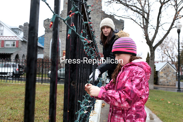 Grace Willmott, 10, uses twist-ties to secure strands of Christmas lights to the fencing surrounding the Gold Star Mothers Memorial in Trinity Park in Plattsburgh, while her mother, Alison, a Dannemora Federal Credit Union employee, holds the lights in place. Members of North Country Veterans Association Post 1 and Dannemora Federal Credit Union decorated the memorial to pay tribute to veterans and current military personnel on behalf of the Clinton County Chapter 30 American Gold Star Mothers. The annual lighting ceremony will take place at 5 p.m. Wednesday, Dec. 7, in Trinity Park and is open to all. GABE DICKENS/P-R PHOTO 11-30-2016