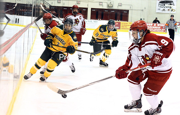 ROB FOUNTAIN/STAFF PHOTO 11-21-2016<br /> Plattsburgh State's Kayla Meneghin (9) scoops up the puck along the wall with Oswego's Victoria Rankin (7) chasing during an ECAC West women's hockey game Sunday at Stafford Ice Arena.