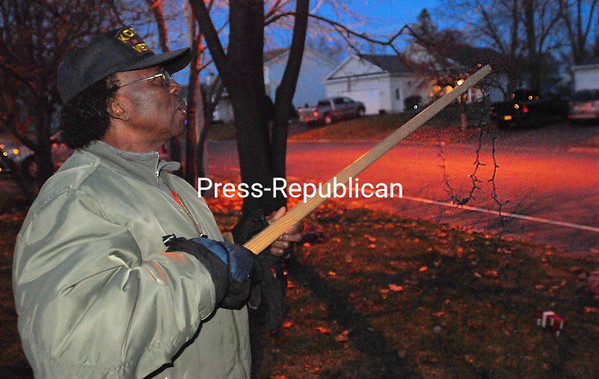 """ROB FOUNTAIN/STAFF PHOTO 11-30-2016<br /> Shedrick Jenkins uses a 2-by-2-inch board to hang Christmas lights on the trees outside his home on Cogan Avenue in Plattsburgh. """"I usually start decorating after Halloween, but I was busy,"""" he said. """"I'll get it done."""""""
