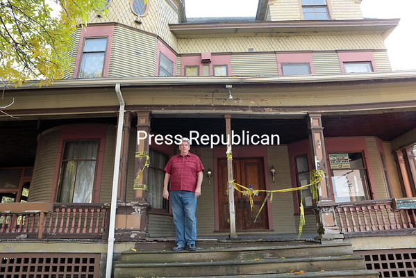 GABE DICKENS/P-R PHOTO 11-5-2016<br /> <br /> Tom Lavin, co-founder of the Adirondack Regional Theatre, stands on the dilapidated porch of a historic 19th-century building at 115 Court St. in Plattsburgh, which has been abandoned for the past seven years. It will be the first official home of the theater company, following repairs and upgrades.