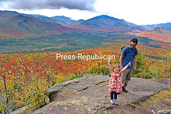 JOANNE KENNEDY/P-R PHOTO 10-14-2016 Lilah Starr of Saranac Lake celebrates reaching the summit of Mount Van Hoevenberg with her dad, David, on a recent day, when the fall colors were close to peak. Lilah hikes with her dad often and said it was gross when they came across garbage left by other hikers, so they cleaned it off the trail. The trailhead for the 2860-foot peak is located on South Meadow Road, 5 miles outside of Lake Placid.