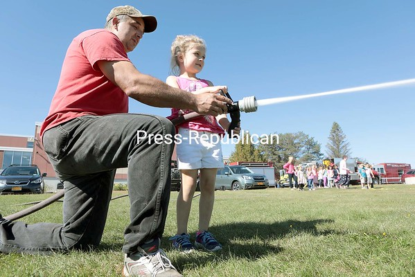 GABE DICKENS/P-R PHOTO 10-10-2016<br /> TJ Strack, the assistant fire chief at the Saranac Fire Department, helps Bella Lucia, a kindergartner with Megan Breton's class, hold a fire hose during fire prevention training at Saranac Central School Friday afternoon. Students also had a chance to experience what it's like to be in a room filling with smoke with the smoke trailer.