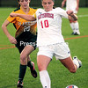 Plattsburgh State's Madeline Saccocio (10) looks to send the ball up field with Clarkson's Camryn Careccia (20) in pursuit during a women's soccer game Tuesday at the Plattsburgh State Field House.<br /> ROB FOUNTAIN/STAFF PHOTO 10-5-2016