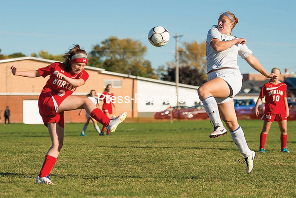 Timothy Behuniak/PR-Photo 10/14/16 Moriah's McKenzie Sprague (left) follows through on a kick as Seton Catholic's Gretchen Zalis (right) looks to defend Wednesday in girls' Northern Soccer League play in Plattsburgh.