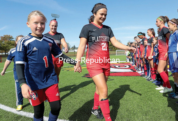 GABE DICKENS/P-R PHOTO 10-16-16 Members of the Plattsburgh Football Club march onto the turf, each paired with a player from the Plattsburgh State women's soccer team, prior to a game Saturday afternoon at the Field House Athletic Complex in Plattsburgh.