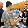 ROB FOUNTAIN/STAFF PHOTO 10-7-2016<br /> During the recent College Night at the SUNY Plattsburgh Field House, Brian (left) and Adam Gallucci talks with Joe Gugino of Endicott College about attending that university. More than 100 college admission representatives were on hand to network with prospective students about their institutions, financial aid and applications. Students also collected college catalogs, obtaining information on requirements, scholarships, programs, athletics and more. More than 2,000 students were expected to attend from Clinton, Essex and Franklin counties.