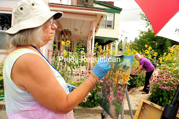 JACK LADUKE/P-R PHOTO 8-23-2016 Artist Cheryl Simeone of Three Mile Bay paints a colorful scene at the Pink House in Saranac Lake during the Plein Air Festival. Pink House owner Chris Winters tends to her flowers in the background. About seventy artists from across the United States and Canada showed up for the annual event, which ran from August 15 to 20.