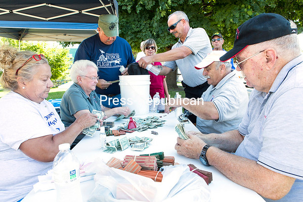 GABE DICKENS/P-R PHOTO 8-24-2016 Volunteers and veterans with North Country Honor Flight count several thousand dollars in coins and bills collected during the organization's recent street drive along City Hall Place and also near Buffalo Wild Wings in Plattsburgh. The goal of $15,000 will help fund the next Honor Flight to Washington, D.C., for 14 military veterans and their guardians, along with medical staff. The next trip is scheduled for Sept. 10.