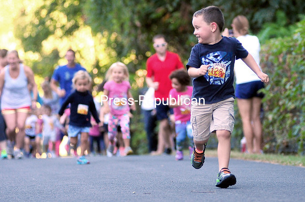 ROB FOUNTAIN/STAFF PHOTO 9-16-2016<br /> Lucas LaPage (128) is all smiles sprinting out in front of the pack in the 1/4-mile race Monday during the Fall Fun Runs series on the Terry Gordon Bike Path in Plattsburgh. LaPage won the race. The event included a 1/4-mile race and a 1-mile race, also pre-stretching and warming up before the races. Next Fun Run is on Monday, Sept. 19 with registration at 5 p.m. and race time at 5:15 p.m. The series is presented by The Clinton County Youth Bureau.