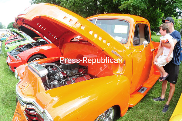 "ROB FOUNTAIN/STAFF PHOTO 8-24-2016<br /> Julio Rodriguez holds up his cousin Camilo Rodriguez to look inside ""The Pumpkin,"" a 1950 Chevy Pro-tour Street Rod, Sunday during the Antique/Classic Car Show and Craft Show at St. Patrick's Church in Rouses Point. Proceeds from the event benefit the church."