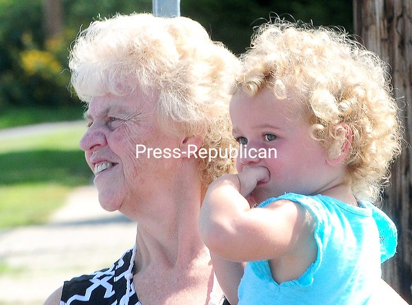 ROB FOUNTAIN/STAFF PHOTO  9-5-2016<br /> Emmie Belair and her great-grandmother Sandy Belair watch the fire trucks roll down Route 11 Sunday during the 58th-Annual Mooers Labor Day Celebration. The event included a chicken barbecue, live entertainment, games, drawings and more. Proceeds will assist the Mooers Volunteer Fire Department with purchasing equipment and supplies.