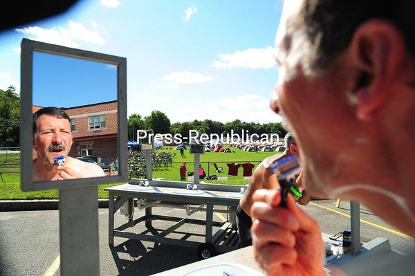 JACK LADUKE/P-R PHOTO 8-25-2016 Mike Ferrara of New Market, N.H., gives himself a shave at an outdoor water basin set up at Petrova School in Saranac Lake to serve the cyclists in the annual Cycle the Adirondacks event taking place this week. Portable showers were also available for the 300 or so participants, who sleep in tents moved and set up by a catering service at each camp location on the 350-mile route. The Cycle Adirondacks participants had a day off Wednesday, and they spent the off hours visiting Saranac Lake and Lake Placid. The weeklong tour, which ends on Saturday in Hadley, near Lake Luzerne, has about double the cyclists it did last year.