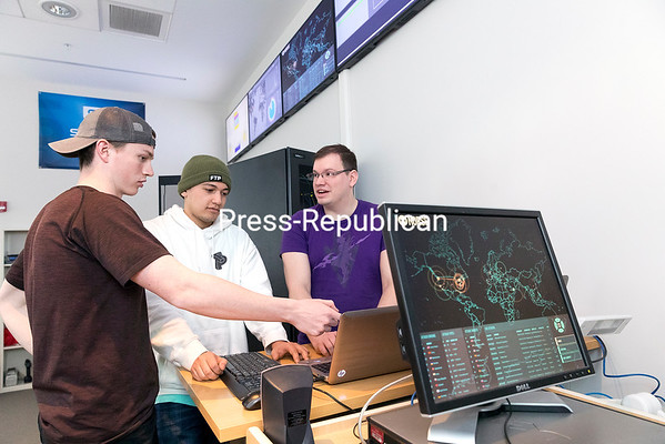 GABE DICKENS/ P-R PHOTO Center for Cybersecurity and Technology Student Co-director Rob Hartman and interns Scott Sparks and Trevor Delong discuss cybersecurity issues at the center's Hackerspace, where students can learn and practice ethical hacking and prevention, in AuSable Hall. The cybersecurity center, headed by Coordinator Cristian Balan, recently hosted an open house to promote the program with students, faculty and community partners.