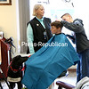 """KAYLA BREEN/STAFF PHOTO<br /> With her service dog, Jack, watching intently, Gillian Duda waits for her son, Connor, to shave the first swath of her hair under the direction of Elizabeth """"Punki"""" Duhaime at Punki's Shear Perfection on Wednesday afternoon."""