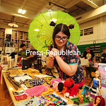 JACK LaDUKE/P-R PHOTO Tamara Wilson holds a colorful umbrella as she looks over her handmade doll clothing, which she was selling at the Malone Comic Con on Saturday. The event was moved thi ...