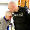KAYLA BREEN/STAFF PHOTO<br /> New York State Trooper Jon Duda kisses his wife, Jill, on her newly shorn head at Punki's Shear Perfection Salon in Plattsburgh on Wednesday afternoon. Gillian, who is paraplegic but is able to walk by use of her hip flexors and arm crutches, will have surgery Friday to end the extreme pain she has suffered for 13 years. One outcome, however, would leave her in a wheelchair for the rest of her life. A State Police escort took Jill to the salon, where Jon, the couple's son, Connor, and a number of troopers had their hair shaved off, too, in a gesture of support.