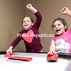 GABE DICKENS/P-R PHOTO<br /> McKenna Booth (left), 5, and Emma Calkins, 6, celebrate scoring a goal against their opponents during a friendly but competitive game of air hockey during a recent Parents Night Out at the Plattsburgh Church of the Nazarene. The event, which is free and open to all infants and children up through sixth grade regardless of church affiliation, takes place from 6 to 9 p.m. on the first Friday of every month through June and starting up again in October.