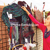 """Lis Barsuglia-Madson hangs some of her Scandinavian woven apparel at the annual Willsboro Folkcraft Fair. Although cheaply made, factoryproduced woven goods are readily found, """"most people can tell the difference, and these will last a long time,"""" said Barsuglia-Madson, who creates Scandinavian wool woven apparel and rugs. """"If you are going to spend the time like I do, you want the best quality. I like to have full control."""" Other items at the craft sale, which benefits Paine Memorial Library, included wood, photography, ceramics, jewelry and stained glass.<br /> ALVIN REINER/ P-R PHOTO"""
