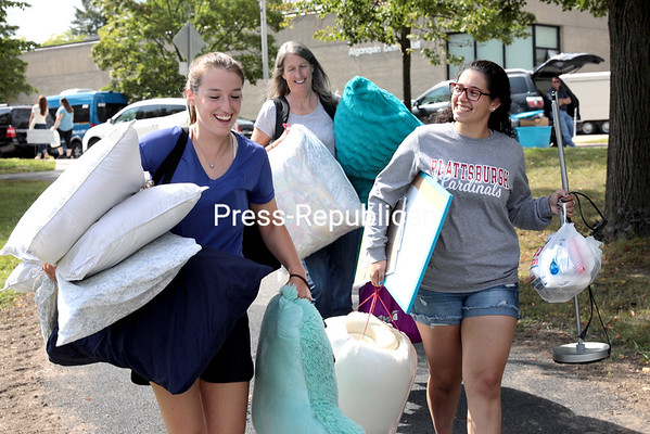 Canton residents and SUNY Plattsburgh freshmen Kelli Cougler (left) and Milaglos Smith (right), along with Cougler's mother, Kathy, move their belongings into their dorm room on the campus in Plattsburgh Saturday afternoon. More than 5,000 students are expected back in the city over the weekend in preparation for the start of classes Monday morning.<br /> GABE DICKENS/ P-R PHOTO