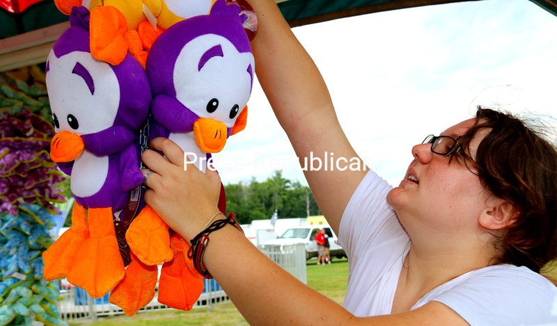 """Kat Schumacher hangs prizes for the duck pond game booth at the Essex County Fair in Westport. """"This is my first year on the road, and I love it,"""" the 22-year-old Long Island native said. """"I had worked at a fair near home and had also tried retail but I have left that and never looked back."""" The fair continues through Sunday at the fairgrounds in Westport.<br /> ALVIN REINER/ P-R PHOTO"""