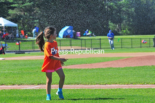 Tanner Winklesas, 5, twirls underneath a shower of water as her father, Plattsburgh RedBirds coach Joe Winklesas, sprays down the field with a hose during the Empire Professional Baseball League All-Star game Sunday at Chip Cummings Field in Plattsburgh.<br /> KAYLA BREEN/ STAFF PHOTO