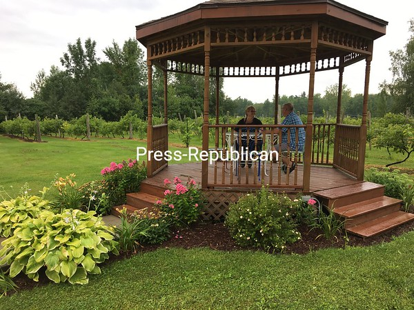 Mary and Gilles Fortin relax in the gazebo at Amazing Grace Vineyard and Winery in Chazy. The flowers, grape vines and tree lines provide a tranquil atmosphere.<br /> DAN HEATH/ STAFF PHOTO