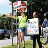 Patti Hartshorn (left) and Aubrey Frenyea hold up their homemade signs and wave to passing drivers who honk their horns in support during a unity rally to support social justice and civil rights at Trinity Park in Plattsburgh.<br /> STAFF PHOTO/ KAYLA BREEN