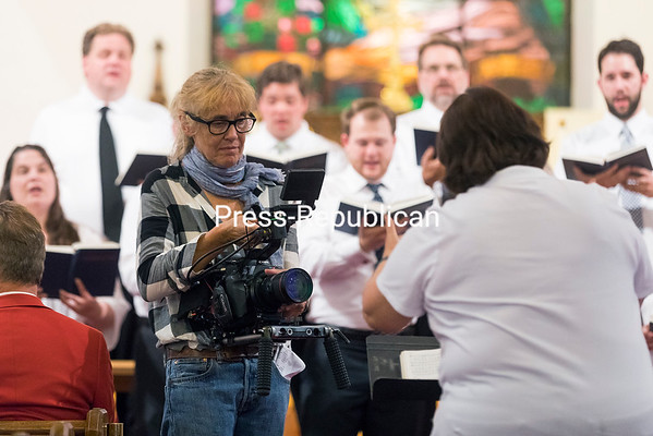 Cinematographer Cassie Farrell records Trinity Music Director Margaret Meyer conducting the choir as they perform.<br /> GABE DICKENS/ P-R PHOTO
