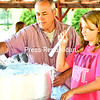 Bill Trudeau pours the cotton candy mix into the bowl while 12-year-old Liberty Bourque waits to wind the blue whipped sugar onto the paper cone Sunday during Altona's Blueberry Festival at Holy Angels Church. Other events included a breakfast buffet, silent auction, theme baskets, pie-raffle wheel, tours of the power house at Feinberg Park, speakers, exhibits and an Alice T. Miner movie.<br /> KAYLA BREEN/ STAFF PHOTO