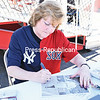 "Linda Ruth Tosetti signs a picture of her grandfather George Herman ""Babe"" Ruth Sunday at Chip Cummings Field in Plattsburgh.<br /> KAYLA BREEN/ STAFF PHOTO"
